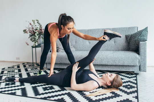 Fit young woman doing stretching exercises with the help of personal trainer at home