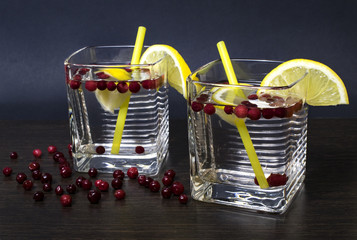 A glass with a cooling drink. Lemon with a glass. Summer drink. Close-up. Dark background.