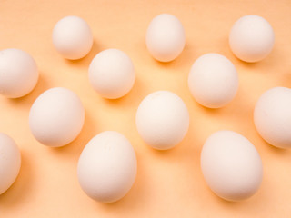 White easter eggs on pastel yellow background close up macro.