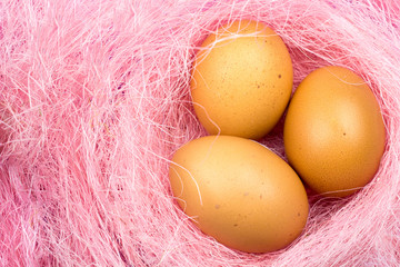 Easter yellow eggs in pastel pink nest close up. Top view.