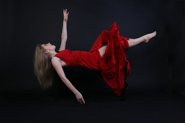 A horizontal image of a floating girl wearing a red dress on a black background. Could be used as a graphic source for a post production of fine art portraits/projects or any other commercial use.