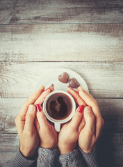 A cup of coffee in the hands of lovers. Silhouette in a cup.  Selective focus.