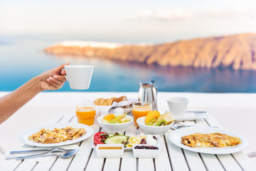 Wall Mural - Breakfast woman drinking coffee at luxury hotel resort restaurant table Mediterranean sea view in Santorini, Oia, Greece. Female hand holding coffee cup at morning brunch. Eggs, fruit salad plate.