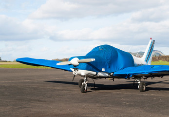 Small sport airplane stay parked on airport runway