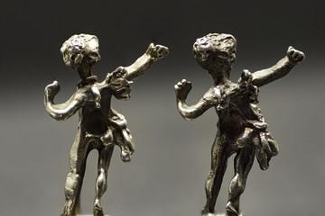 two metallic figurine angels are dancing