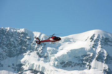 Poster Helicopter Helicopter flying over Alps peaks, Switzerland