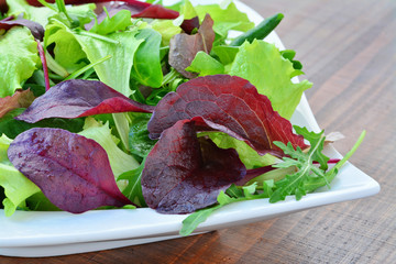Fresh spring salad of mixed greens, mesclun, arugula, mache, lettuce, tender leaf vegetables in plate over wooden table
