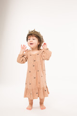 Cute little girl in beige dress with gold crown isolated on white background. Portrait of happy little girl.
