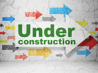 Web design concept:  arrow with Under Construction on grunge textured concrete wall background, 3D rendering