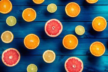 Oranges limet lemon and grapefruit on blue table.
