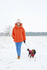 Full length shot of a happy woman walking her small dog outdoors on snowy landscape in winter.