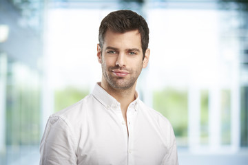 Young man portrait. Portrait of handsome young businessman looking at camera while standing at office.