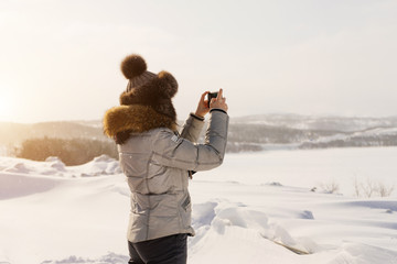 woman in winter suit photographing winter landscape