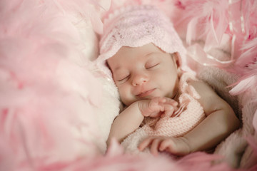 New born baby sleeping on a soft fur background and covered in pink feathers with a soft focus to add elegance.