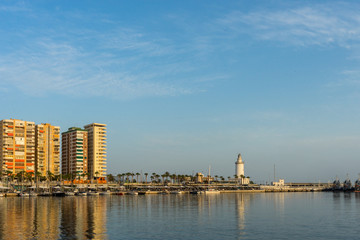 White lighthouse and the tall buildings of Malaga with their reflections in Malaga, Spain, Europe
