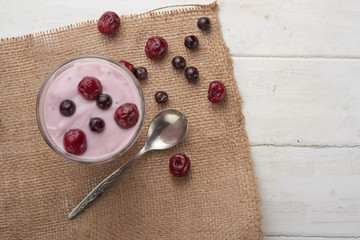 yogurt in a glass with berries on sacking and texture