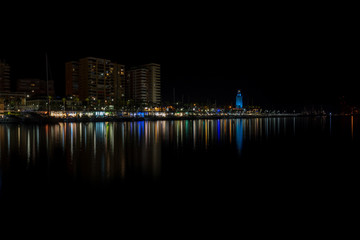 View of Malaga city and lighthouse and their reflections on water from harbour, Malaga, spain, Euope at night
