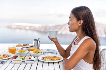 Wall Mural - Luxury resort woman drinking coffe at breakfast table looking at Mediterranean sea view from hotel outdoor restaurant balcony or room. Tourist eating food relaxing, healthy brunch.