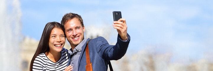 Aufkleber - Happy multiracial couple taking selfie photo with phone on spring travel holiday. Europe vacation travelers traveling in city banner panorama.