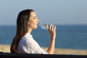 Woman drinking water from a bottle on the beach