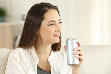 Woman holding a soda can looking away at home