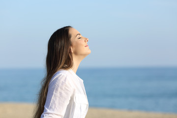 Woman relaxing breathing fresh air on the beach