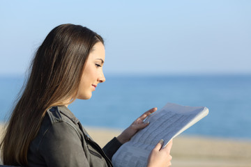 Woman relaxing reading a newspaper on the beach