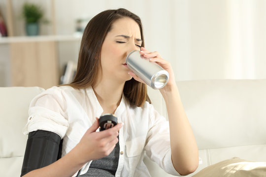 Woman with low blood pressure drinking sweet soda