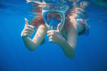 Woman snorkeling mask in blue sea. Snorkeling woman in full face mask.