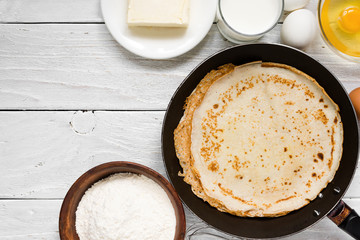 Stack of pancakes on frying pan with ingredients on white table