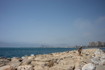 A father helping his son walk on the rocks on the Malagueta beach in Malaga, Spain, Europe