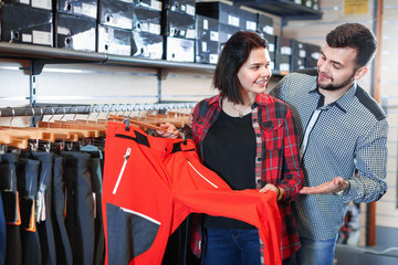 Young couple choosing touristic trousers in sports clothes store