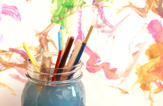 Paint brushes soaking in a glass jar of soapy water