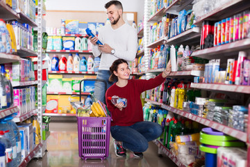 two active adult people in good spirits selecting detergents in the store