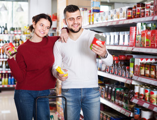 Happy young couple choosing purchasing canned food for week at supermarket