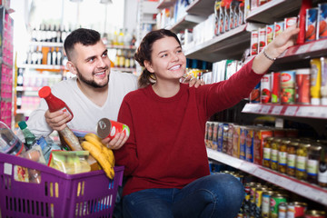 Smiling young couple purchasing tinned food