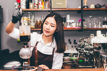 Women Barista making coffee on syphon coffee maker in the cafe
