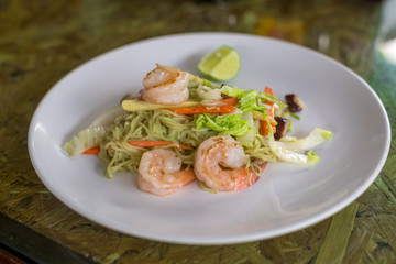 Green Noodle stir fired with shrimp, lettuce, corn and carrot in white plate on wooden table, Thai food