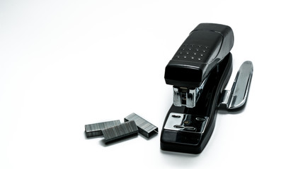 Black stapler and staples that have been used in the office for a long time. Black stapler and staples on white background with copy space. Old staff of the office and valuable personnel concept.