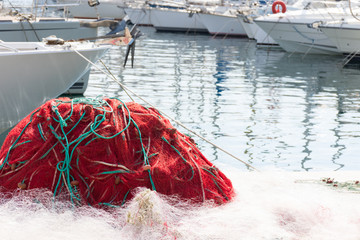 A Tangle of Red Fishing Net from a commericial fishing boat with the bows of other boats and the rippled water of Vieux Port in Marseilles in the background.