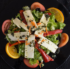 Fresh Salad with greens, mozzarella cheese, tomato and orange wedges, red peppers and shredded carrot on a black plate and black placemat.