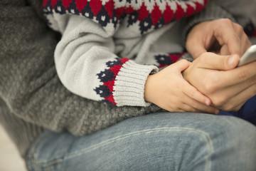 お父さんの膝に乗って、手を握る男の子。