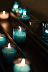 Lit Religious Votive Candles in a Catholic church. The candles glow brightly in the dimly lit interior.