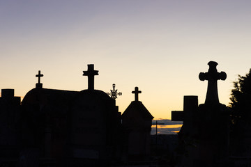 Sunset at Roussillon's Cemetery with the silhouettes of the mausoleums topped with crosses  against a yellow, gold and lavender sky.