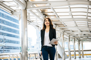 Beautiful young businesswoman walking outside public transportation station. Businesswoman traveler with suitcase on the way to the airport.