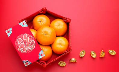 Group of orange tangerine in Chinese pattern tray and envelope packet ang pow with gold ingots on red table top. Chinese new year concep.Chinese Language on envelop is happiness,on ingot is wealthy.