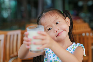 Smiling little asian girl drinking milk in restaurant at the morning.