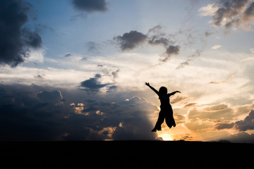 Silhouette of Happy woman jumping and sunset