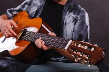 Closeup of man playing acoustic guitar
