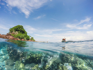 Fishing boat with small island in the sea over coral reef